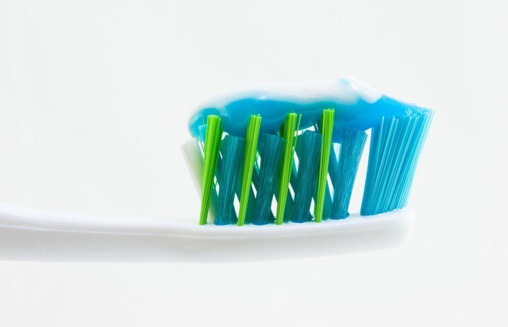 toothpaste on a blue toothbrush with a white background