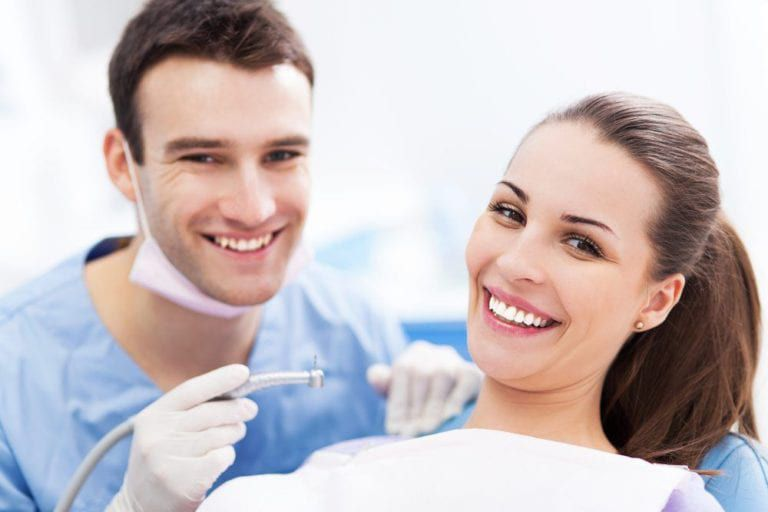 male dentist and female patient smiling