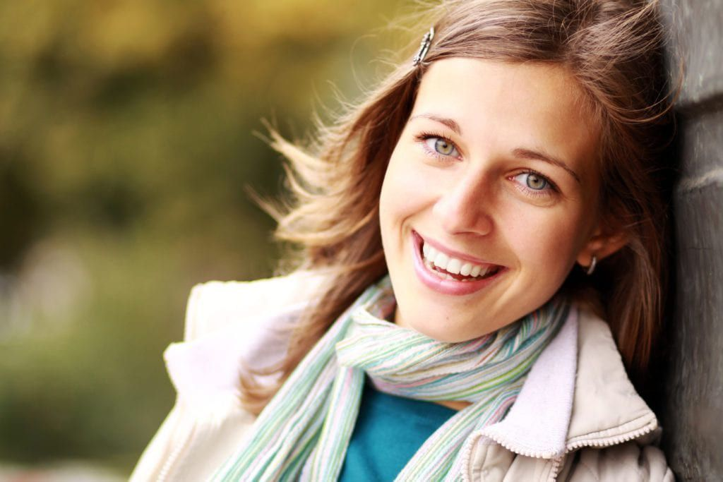 woman leaning against a wall smiling