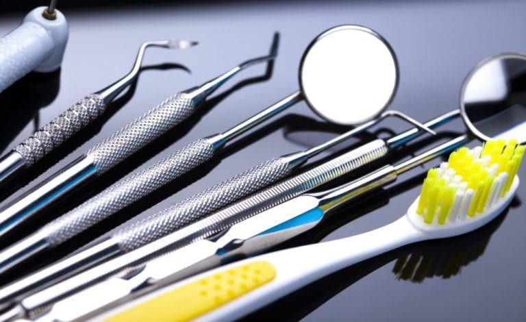 dentist tools besides a yellow toothbrush