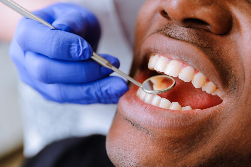 Male patient receiving dental cleaning
