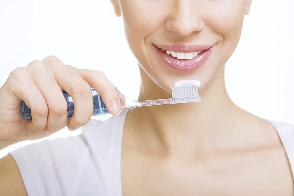 lower half of a woman's face brushing her teeth with whitening toothpaste