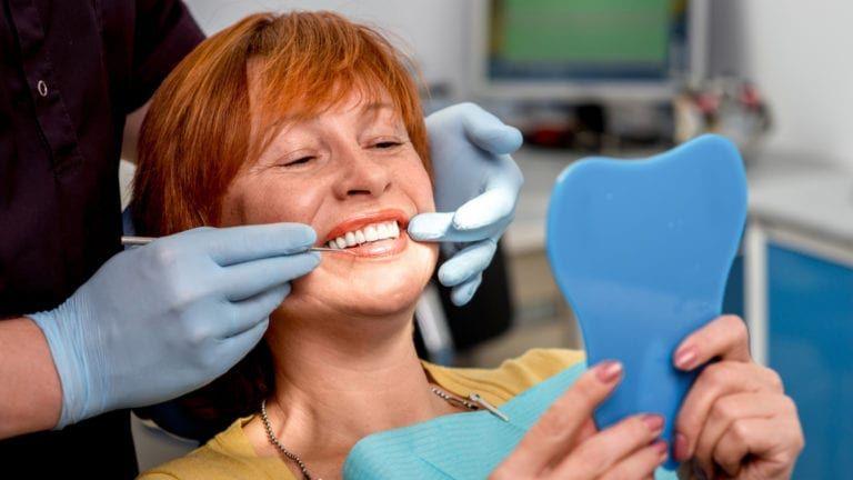Patient viewing new cosmetic dentures