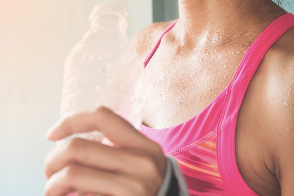 closeup of a water bottle next to a women's chest after working out